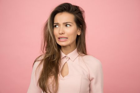 woman with long hair standing in front of pink background