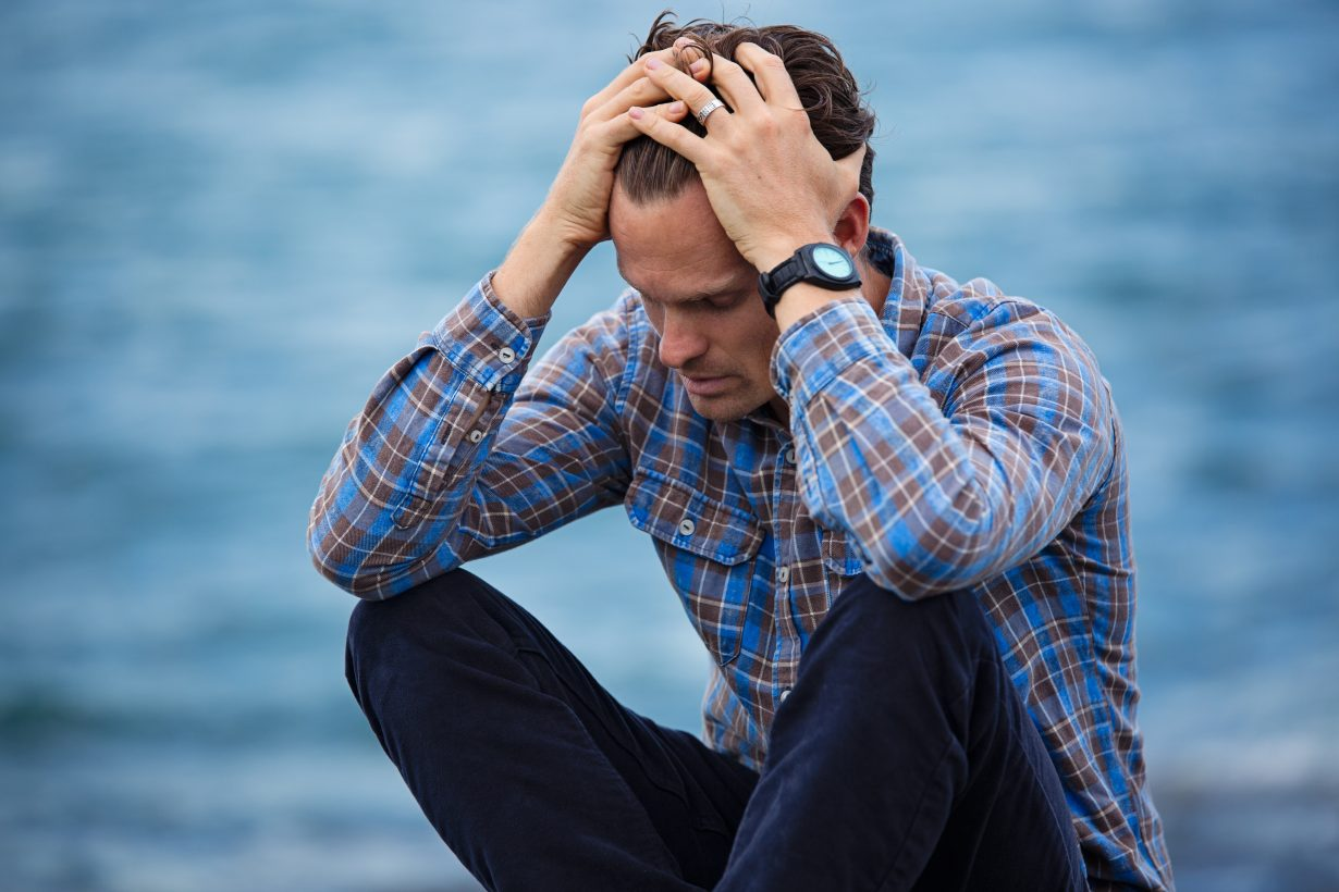 man sitting with hands on head looking stressed