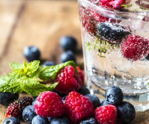 sparkling clear drink in a glass with floating berries inside