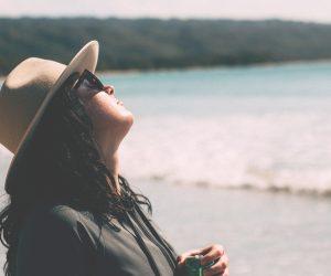 woman on a beach tilting her face toward the sun