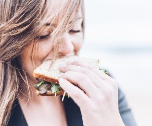 close up of a woman eating a sandwich