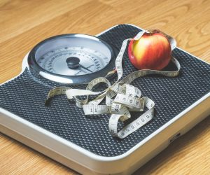 scale with measuring tape and an apple on it
