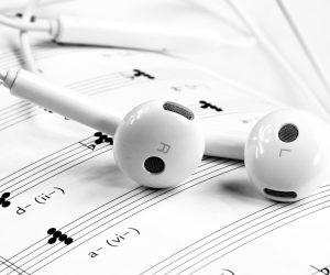 white headphones sitting on sheet music