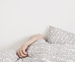 person's arm sticking out over a pile of bed pillows