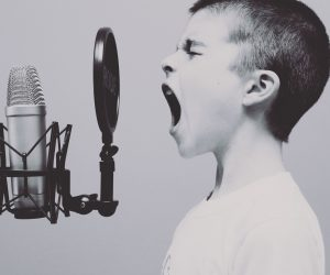 little boy yelling into a pop microphone