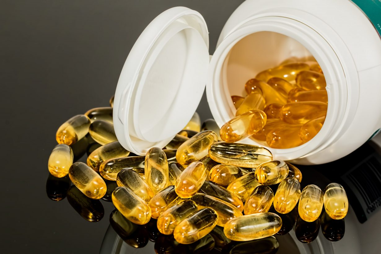 bottle of vitamin d tipped over with pills all around