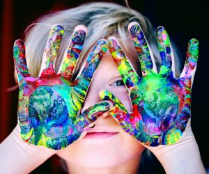 child holding up his hands with paint all over them