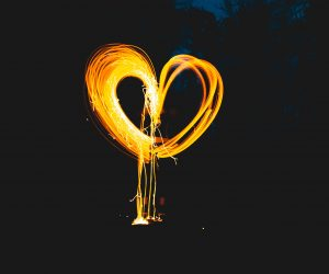 photo of a person making a heart out of a sparkler