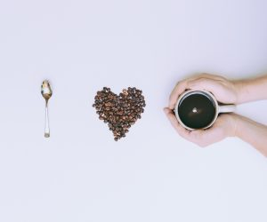 I love coffee spelled using a spoon, a heart made of coffee beans and a person holding a cup of coffee