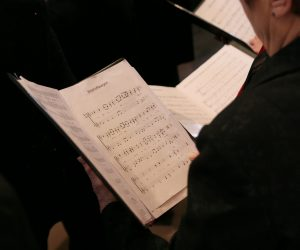 person in a choir holding sheet music