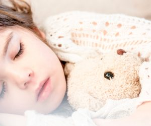 sleeping child holding a stuffed animal