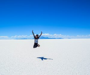 woman jumping up in the air at the salt flats