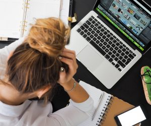 woman anxiously holding her head sitting in front of a laptop