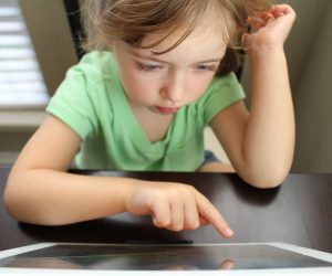 little girl looking at a tablet