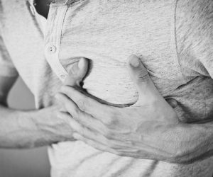 man grasping heart appearing to have a heart attack