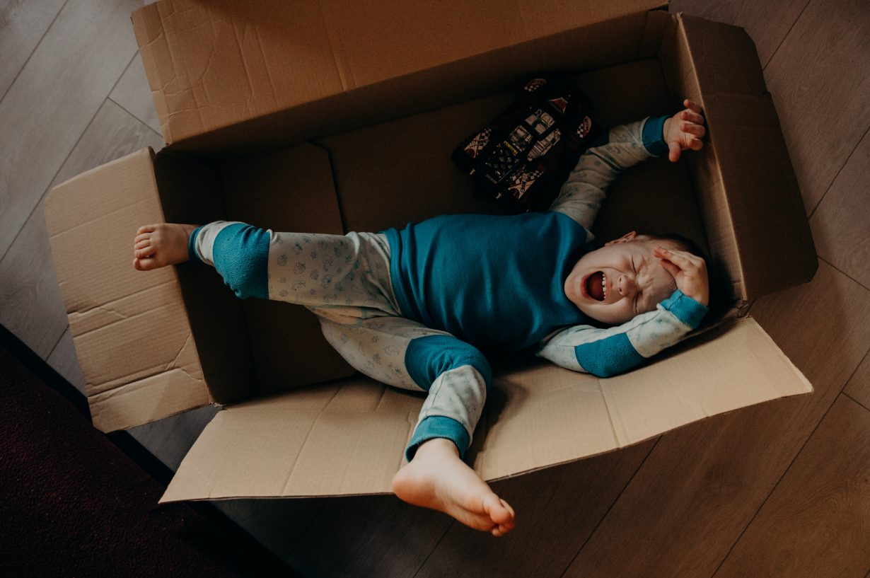 little boy crying in a cardboard box