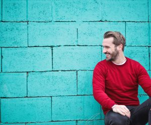 man in red shirt leaning against a teal wall