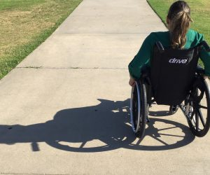woman in wheelchair on a sidewalk