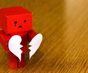 red robot holding a broken heart