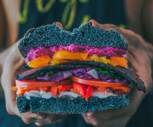 man holding a really colorful vegetable sandwich