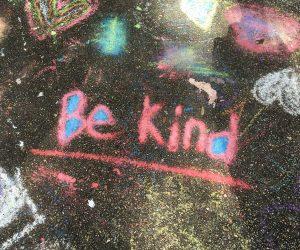 Be Kind written in sidewalk chalk on the ground