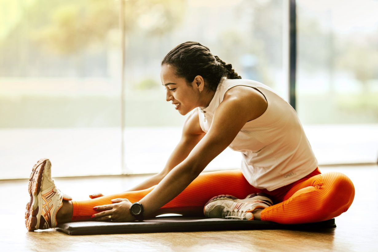woman stretching her leg in athletic clothes