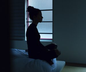 woman sitting on her bed in the dark