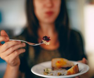 close up of a plate of food with woman in background