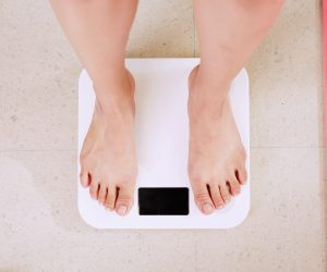 person standing on a white weight scale