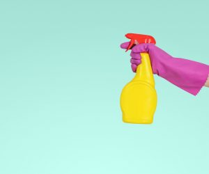 person wearing a pink rubber glove spraying a yellow spray bottle