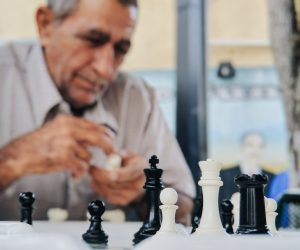 selective focus of a chess set with an older man in the background