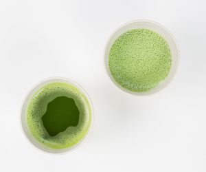 two cups of green tea on a white surface