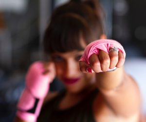 woman wearing pink boxing tape on her hands punching toward the camera