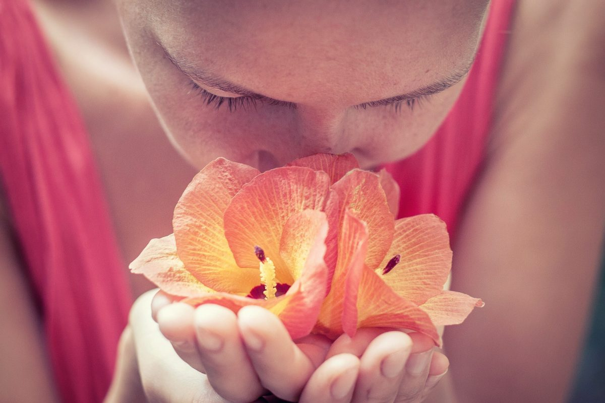 woman holding flowers up to her nose