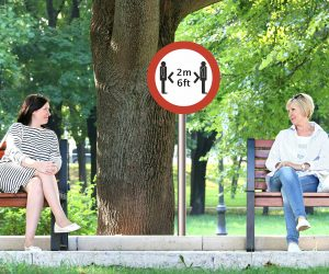 two women sitting 6 feet apart on park benches