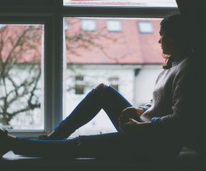 woman sitting on a window sill looking out her window