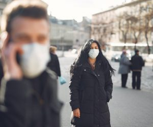 person wearing face mask walking on a street