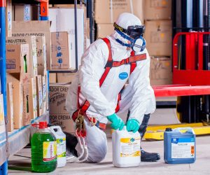 man in white suit working with chemicals