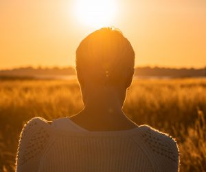 woman facing the sunset in a field
