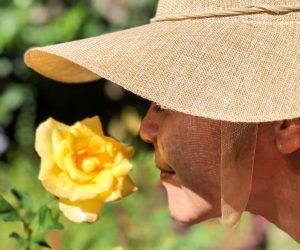 woman sniffing yellow flower