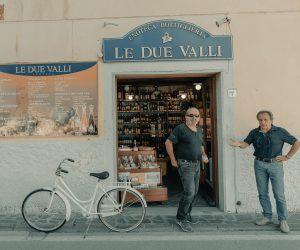 two italian men standing in front of a store