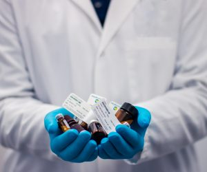 person in a lab coat holding medicine vials
