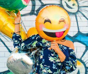 person holding a smiley face balloon