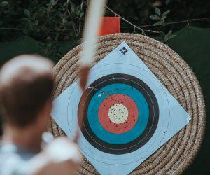 man shooting an arrow at a bullseye target