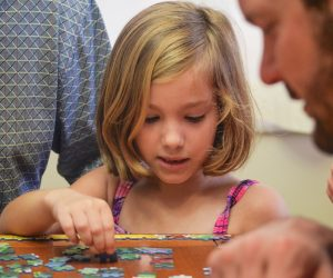 little girl working on a jigsaw puzzle