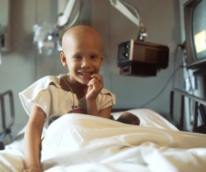 little child smiling in a hospital bed with a bald head