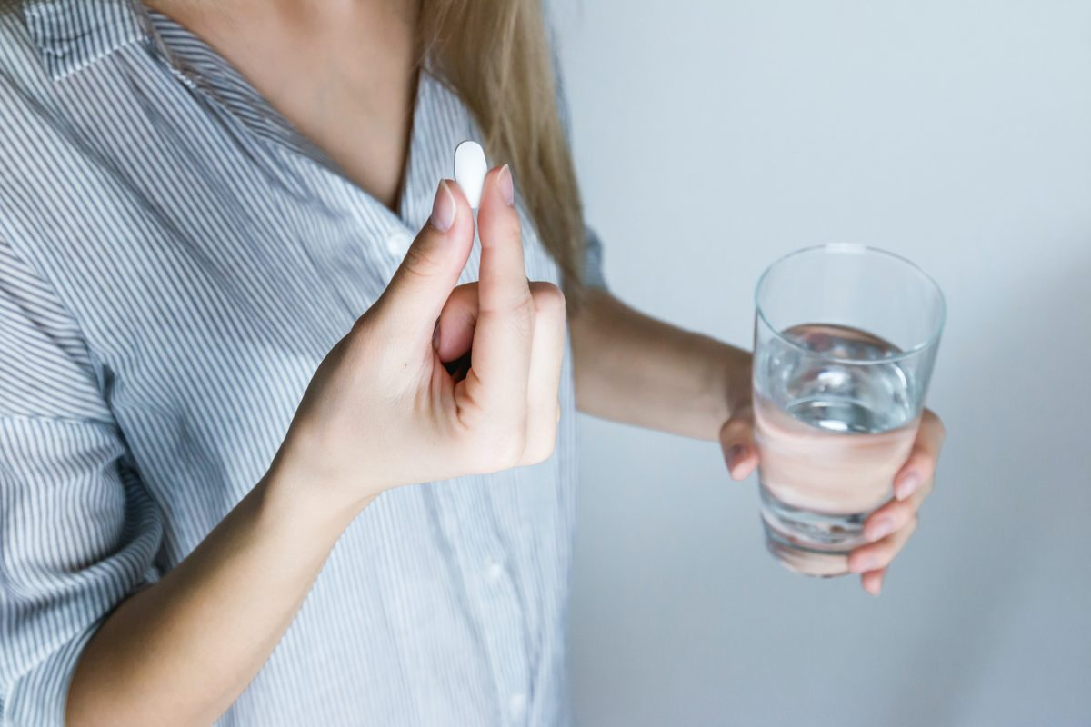 woman taking a pill with a glass of water