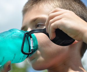 child drinking from a plastic bottle