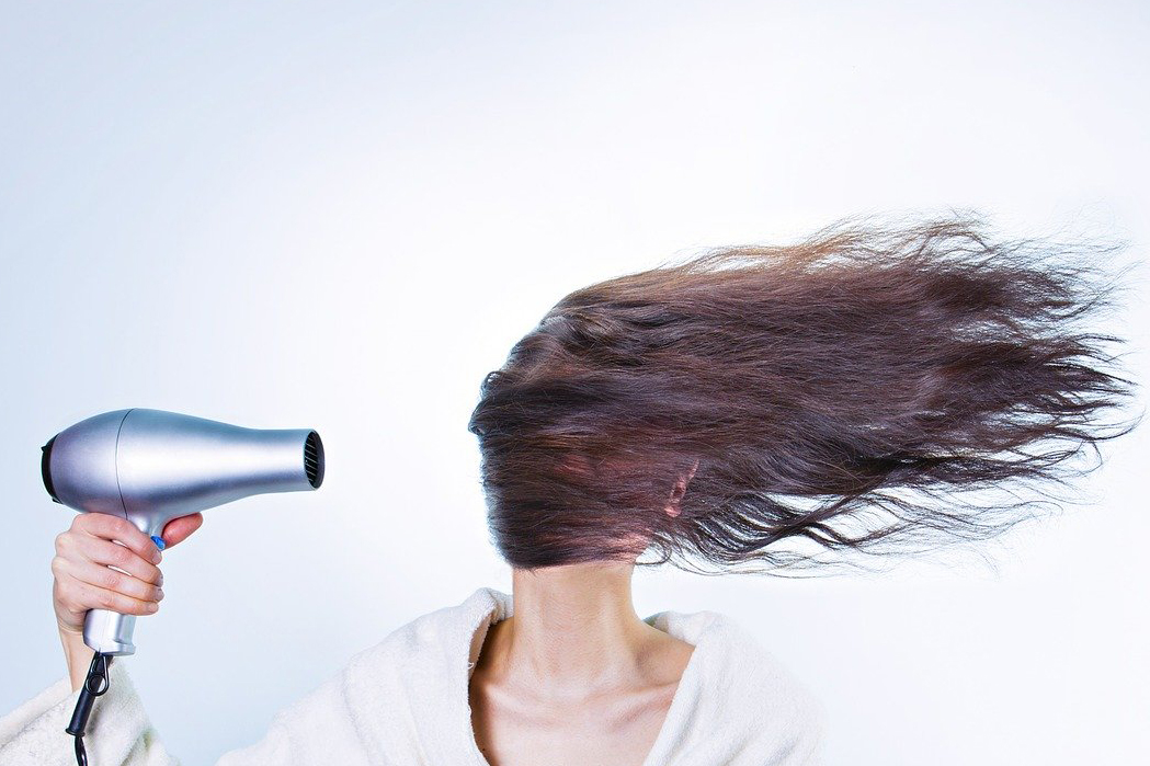 person blow drying their hair in front of their face