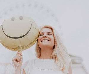 woman smiling while holding a smiley balloon